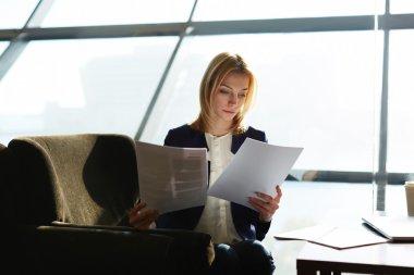 Businesswoman examining paperwork at her desk