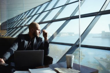 Side shot of handsome successful businessman pensively gazing out of the window thinking about the work plan, attractive young business man looking out of airport hall window, deep in thought stock vector