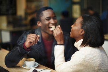 Woman feeding man with dessert cake