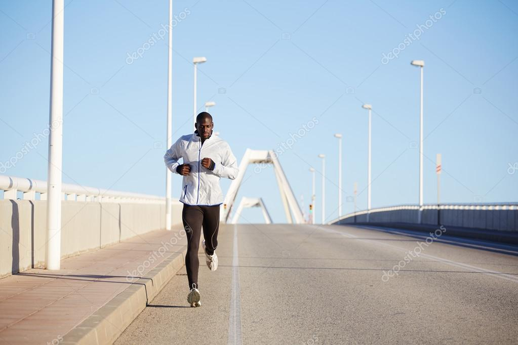 Sportsman dressed in white windbreaker running