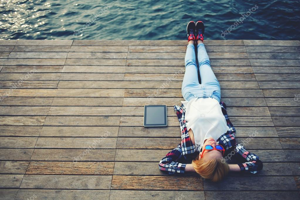 Woman lying on a wooden jetty