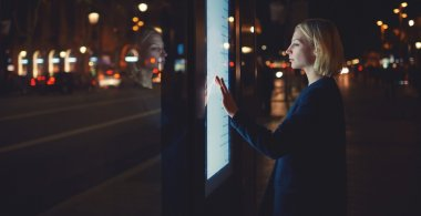 woman using modern urban application of bus stop