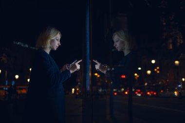 woman touching sensitive screen of smart city bus stop