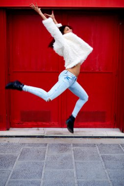 woman jumping on red door background