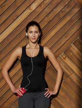woman in sportswear listening music with headphones