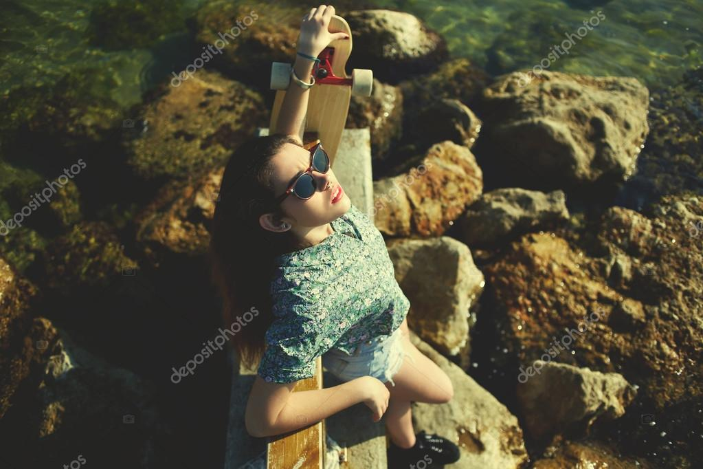 cool woman posing with skateboard near sea