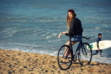 hipster girl relaxing on the beach wit bicycle