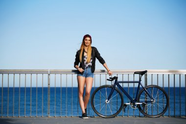 stylish hipster girl standing on the pier with bicycle