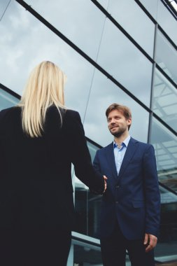 businesswoman shaking hand with smiling employee