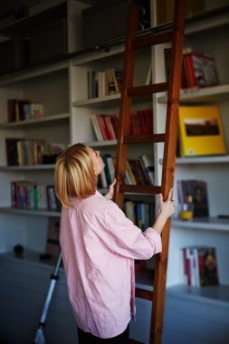 blonde woman climbing on library ladder