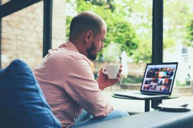 Businessman near laptop while coffee break
