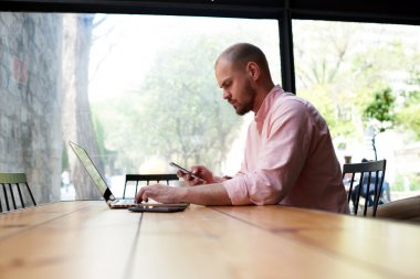 student sitting at wooden table with laptop