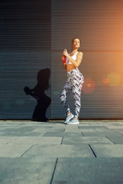 Fit woman with perfect figure with energy drink