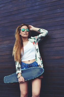teenage girl in sunglasses holding skateboard