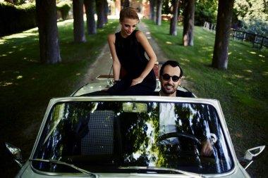Happy couple enjoying a ride on car