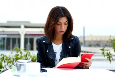 Charming woman with book in restaurant