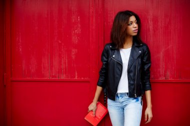 afro american woman posing on red wall