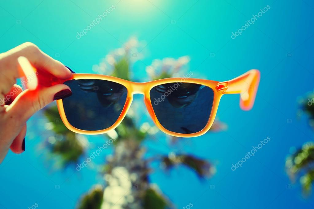 sunglasses against palm tree and sky