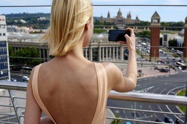 Woman traveler photographing urban view