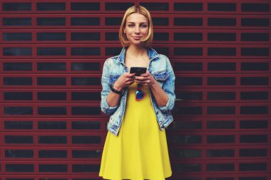 Lovely young woman holding mobile phone in hands and look to the camera smiling