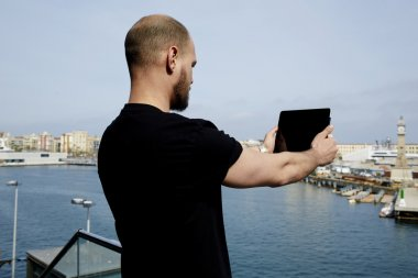 Attractive tourist with digital tablet camera taking picture of beautiful city from viewpoint