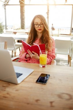Attractive creative freelancer read notebook while sitting at wooden table with laptop laptop computer and cellphone