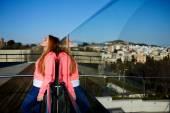 Fotografie Hübsche Frau, stehend gegen Glaszaun
