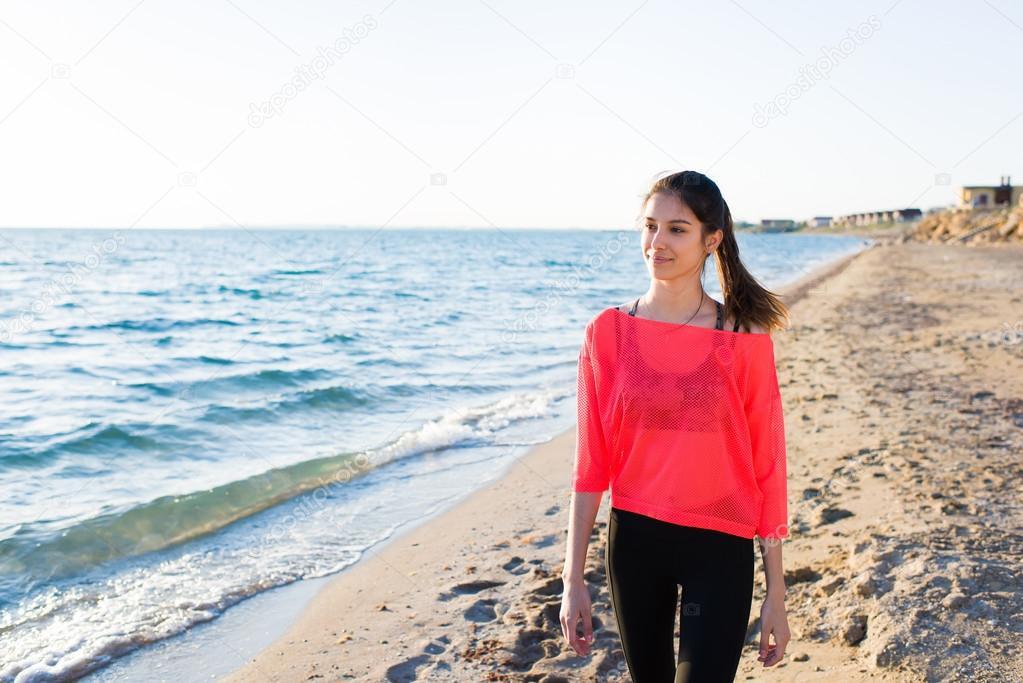 Female runner walking along the beach