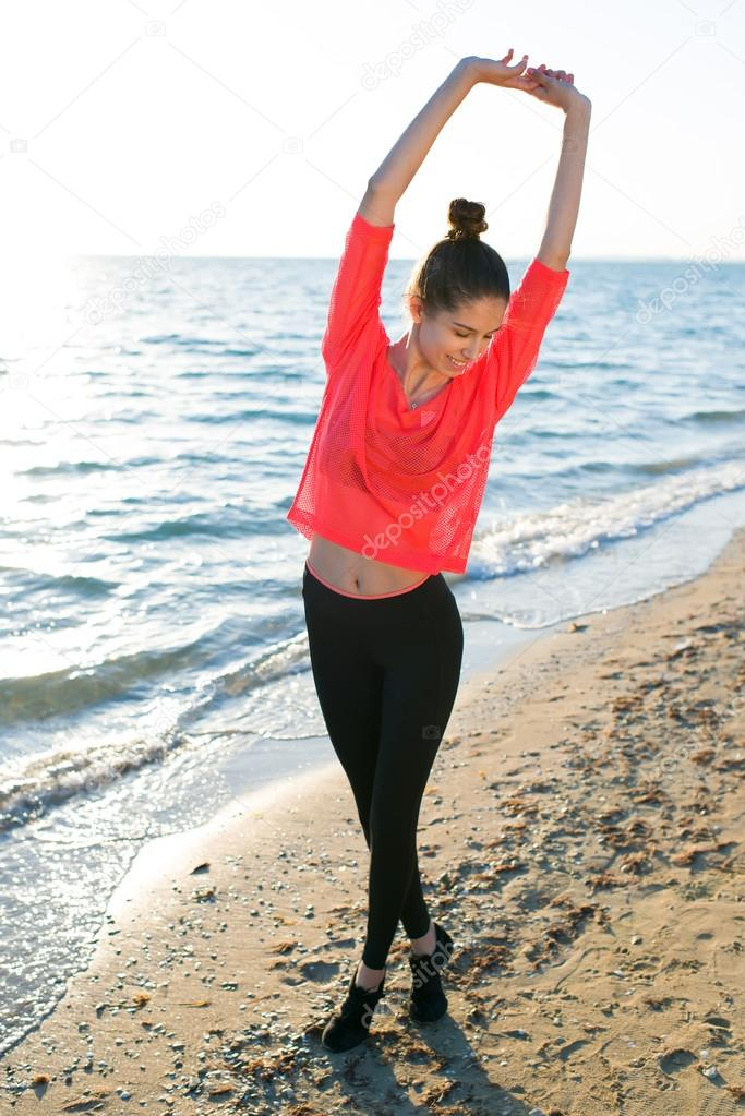 Young fit woman stretching  on the beach