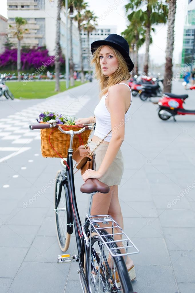 female posing for the camera with vintage bike