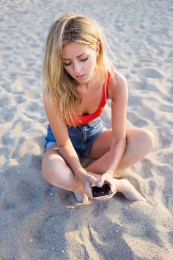 Girl using mobile phone on the beach