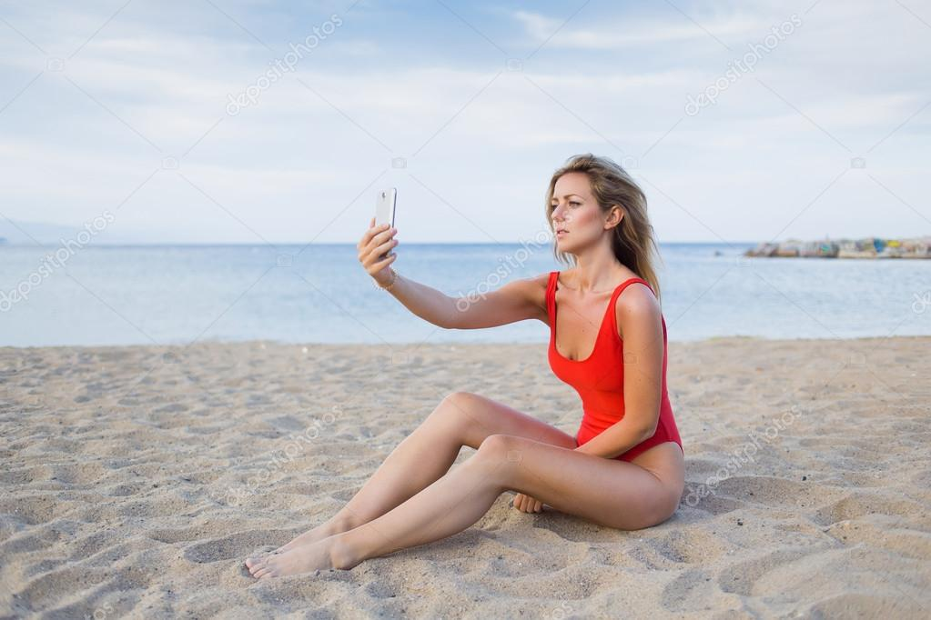 80a08ad7b9 Gorgeous young woman in sexy bikini making self portrait with a cell phone  camera while she sitting on the beach, charming female in fashion red  swimsuit ...