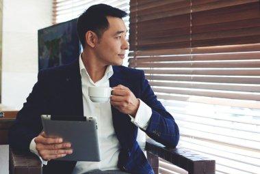 Young confident businessman enjoying coffee