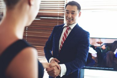 Smiling asian businessman shaking hands