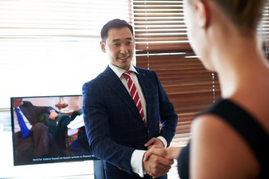 Smiling asian businessman shaking hands