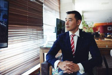 Asian businessman watching television