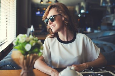 Portrait of lovely young woman dressed in stylish sunglasses looking out coffee shop window with bright smile, happy attractive female waiting for her friends while sitting in modern cafe interior stock vector
