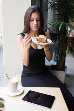 Woman eating dessert in cozy cafe