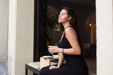 Woman enjoying work break in cafe