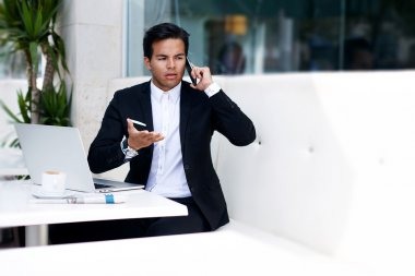 Worried businessman talking on mobile phone