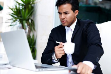 Businessman reading latest news on laptop