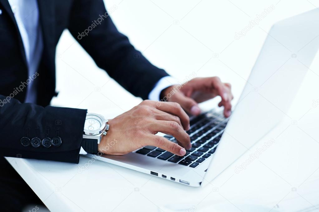 Successful businessman keyboarding on his laptop