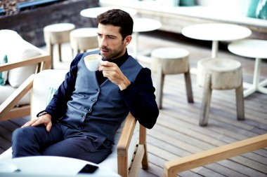 Businessman in suit enjoying a cup of coffee