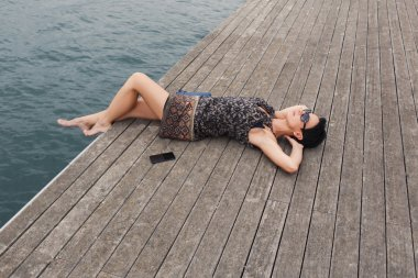 Attractive woman  lying on a wooden pier