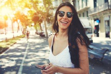 Latin woman in sunglasses using smartphone