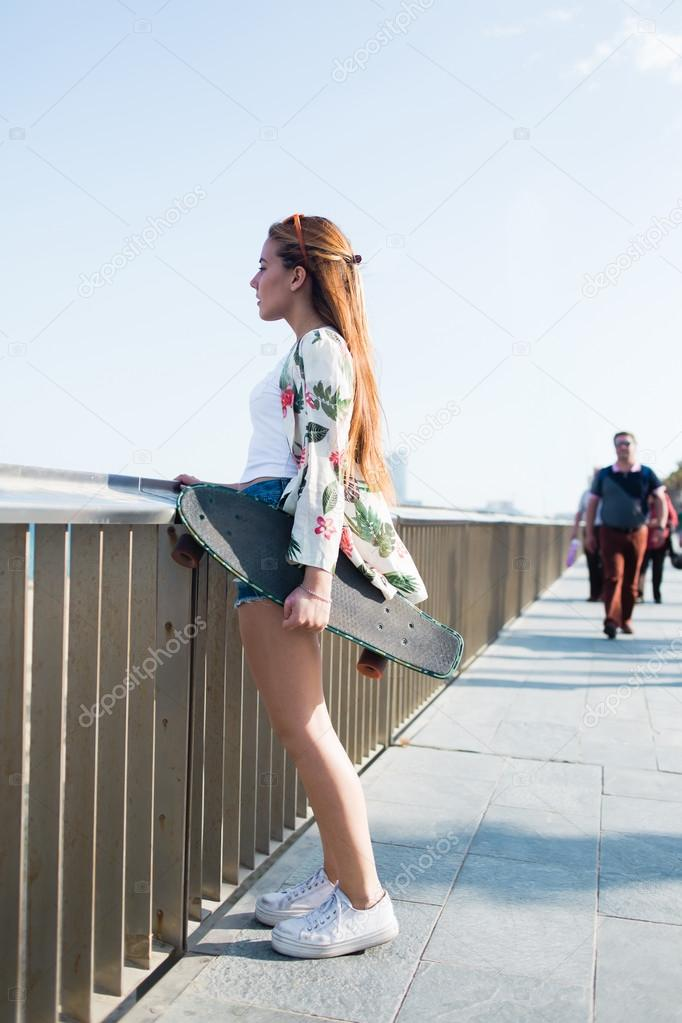 Woman with longboard while standing on bridge