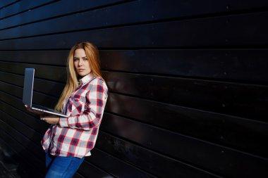 Hipster girl using her net-book outside