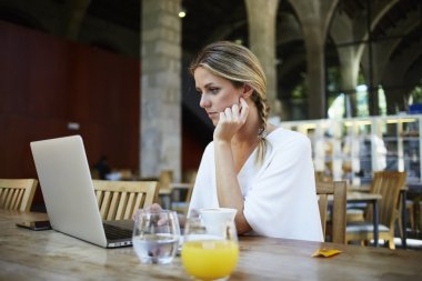 Female freelancer working on net-book in cafe