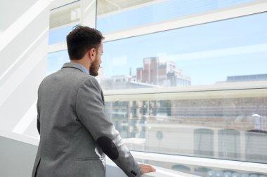 Businessman looking in office window