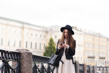 Woman with mobile phone walking on the street